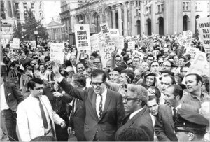 In the 1968 Ocean Hill-Brownsville strike, the AFT's vision of teacher unionism collided with the issue of community control of schools in New York City's Ocean Hill-Brownsville neighborhood.  Racial tensions ran high because the AFT teachers were predominantly white, and the area residents were predominantly black and Puerto Rican.  To its critics, the AFT's actions in the strike made it seem as if the union supported collective bargaining rights for predominantly white teachers at the expense of community control for non-whites in the district. The NEA gained support in the wake of the New York clash, as it appeared more committed to civil rights and progressive reform. Albert Shanker (foreground center with glasses), president of the New York City AFT local leads a strike rally at City Hall in 1968. Credit: The Weekly Nabe
