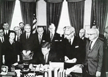 In 1959, Wisconsin became the first state to pass a collective bargaining law for its public employees, largely thanks to significant lobbying from the American Federation of State, County, and Municipal Employees (AFSCME). In 1962, President John F. Kennedy passed his Executive Order 10988, which granted many federal employees limited collective bargaining rights. President Kennedy signing EO 10988. Credit: NALC