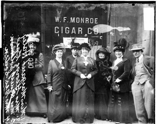 Group portrait of Margaret Haley, Mrs. George Bass, Mrs. Henry Solomon, and Mrs. George A. Soden standing in front of W. F. Monroe Cigar Co., located at 5 South Dearborn Street in the Loop community area of Chicago, Illinois. The women were demanding the resignation of John D. Shoop, Superintendent of the Board of Education. Miss Haley was leader of the Chicago Teachers' Federation.  From Library of Congress
