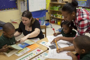 Teacher Sheri McCormick (left) and paraprofessional Shashala Saulsbury work on a reading assignment with students. Credit: UFT