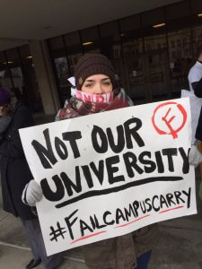 Protestors at KU wear NRA cloth around their mouths, symbolizing their voices being silenced by gun lobbyists. Source: Twitter.